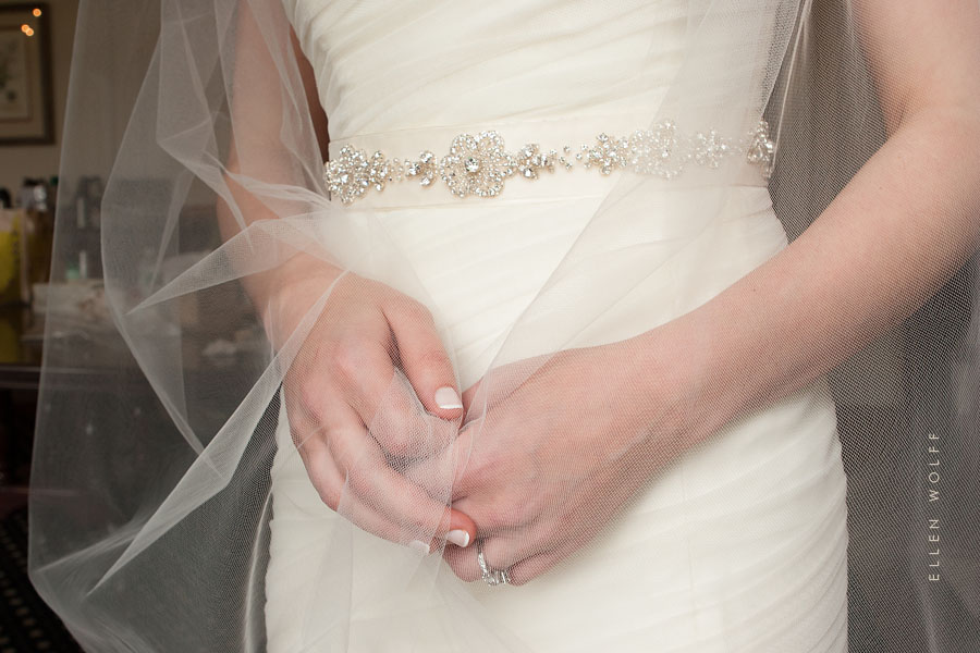 photo of the brides hands, embellished sash, and veil