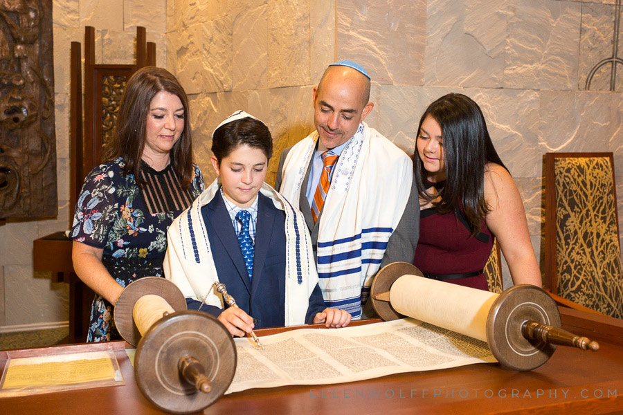 family gathers around the open torah